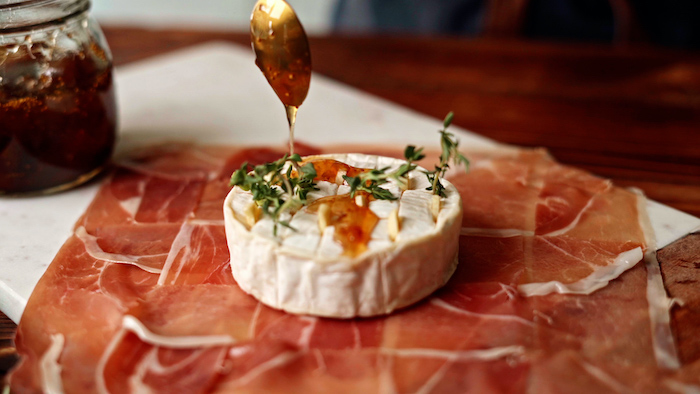 brie cheese covered with jam spread onto prosciutto slices thanksgiving dinner ideas placed on marble cutting board