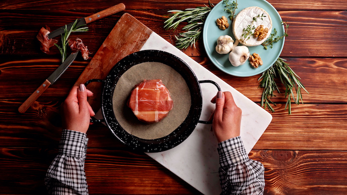 brie cheese covered with prosciutto placed on parchment paper lined baking sheet thanksgiving dinner ideas on wooden surface