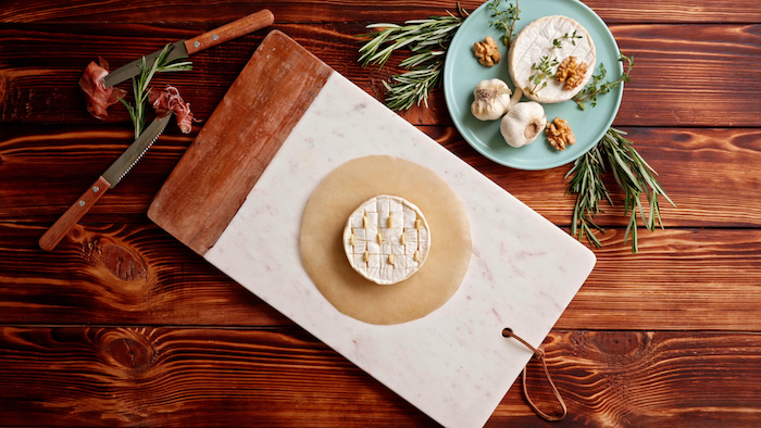 brie cheese with small slits with butter placed on parchment paper on marble cutting board thanksgiving dinner ideas wooden surface