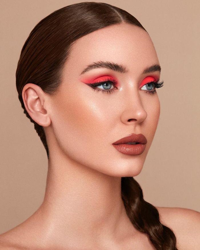 brown hair in side braid winged eyeliner woman with pink orange eyeshadow black eyeliner brown lip gloss