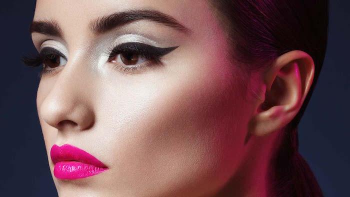 brunette woman with hair in low ponytail cat eye eyeliner silver glitter eyeshadow pink lipstick