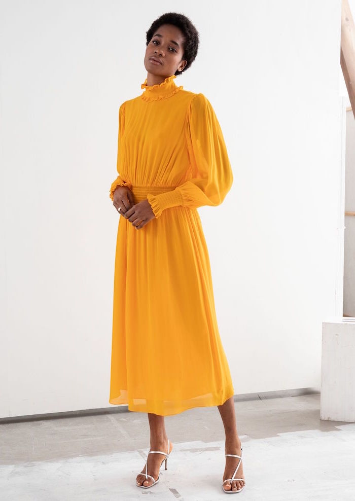brunette woman with short afro wearing yellow dress with puff sleeves how to dress for a wedding silver sandals