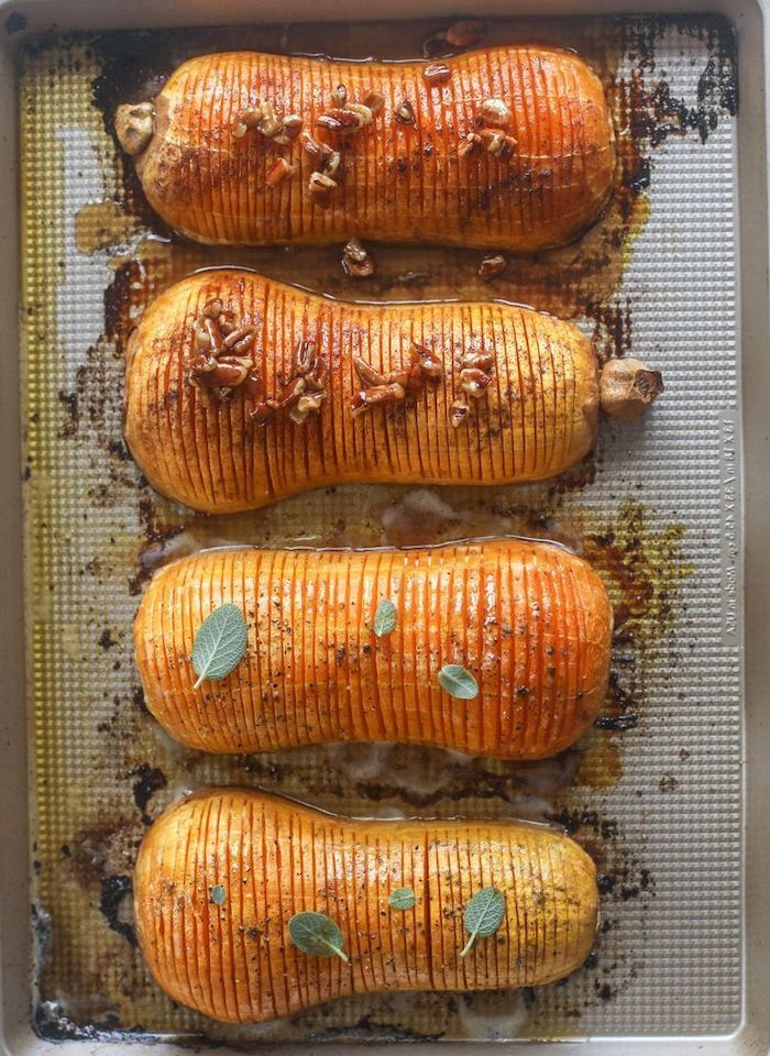 butternut squash with slits covered with walnuts cinnamon placedon baking sheet thanksgiving food ideas roasted
