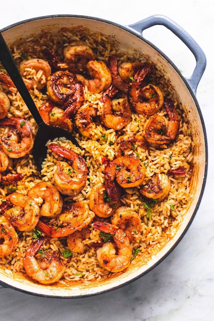 cajun shrimp and rice baked in large skilled stirred with black spoon shrimp dinner ideas placed on marble surface
