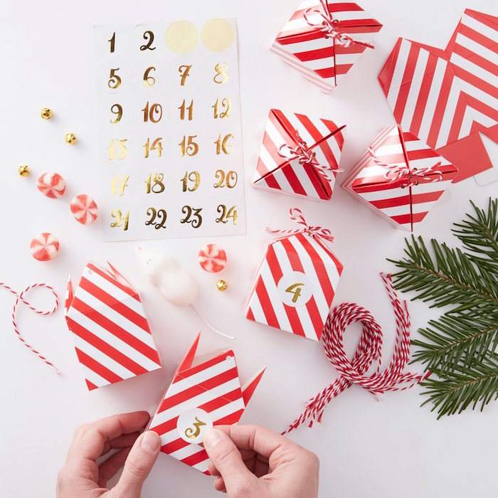 calendar made with red and white take out boxes with golden numbers on them placed on white surface diy advent calendar