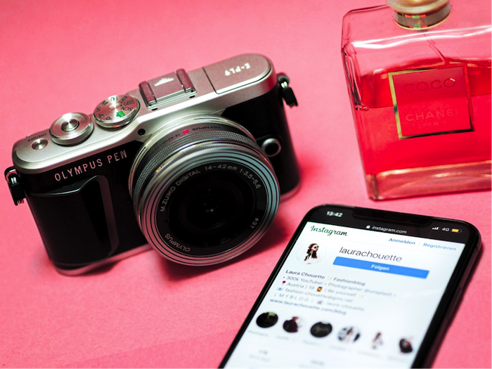 camera olympus pen next to phone perfume bottle placed on pink surface instagram followers