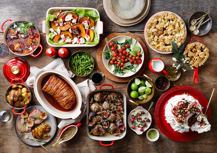 casserole dishes with different meals bowls and plates arranged on wooden table christmas eve dinner