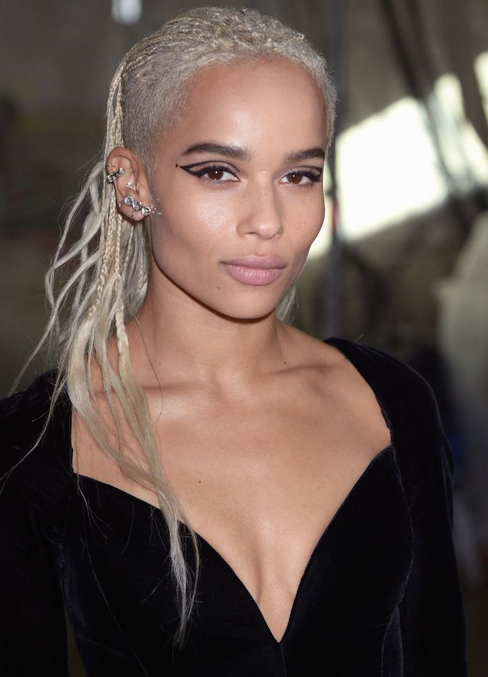 cat eye makeup zoe kravitz with blonde hair lots of ear piercings wearing black velvet dress with deep v neckline