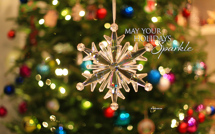 christmas background iphone may your holidays sparkle written next to glass snowflake ornament lights in the background