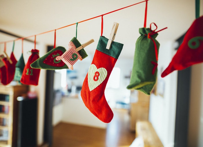 christmas countdown calendar small stockings and bags in red and green hanging from a red string with numbers on them
