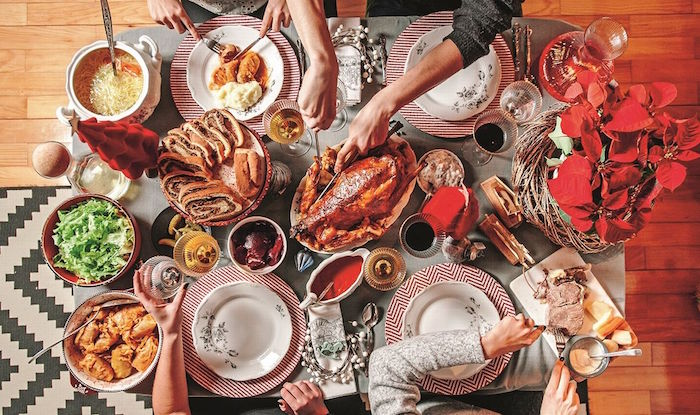 christmas eve dinner four people sitting around table with gray table cloth lots of dishes on it in bowls and trays