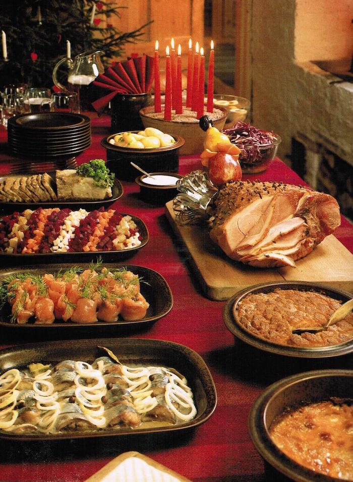 christmas eve dinner ideas table with red table cloth different dishes on the table in black trays and plates baked ham on wooden cutting board