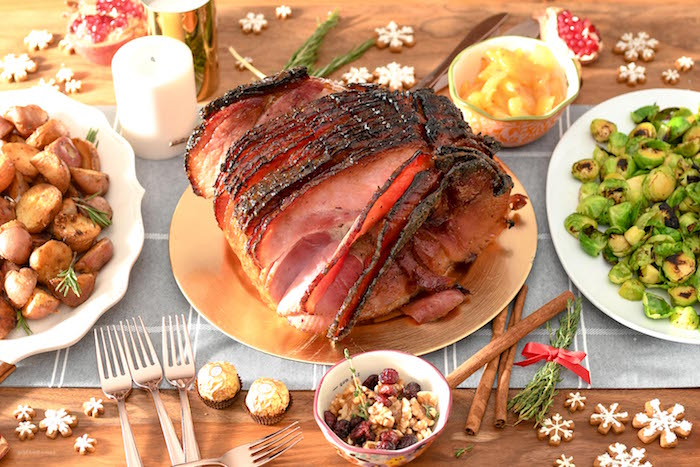 christmas ham sliced placed on golden tray christmas dinner 2020 two plates with potatoes and brussels sprouts on the sides