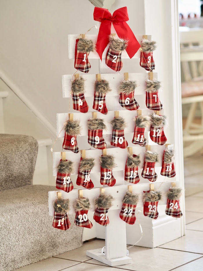 christmas stockings hanging from white wooden boards arranged in the shape of christmas tree advent calendar ideas