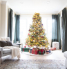 christmas tree decoration ideas placed in front of window with warm lights red gold baubles lots of presents underneath on small rug
