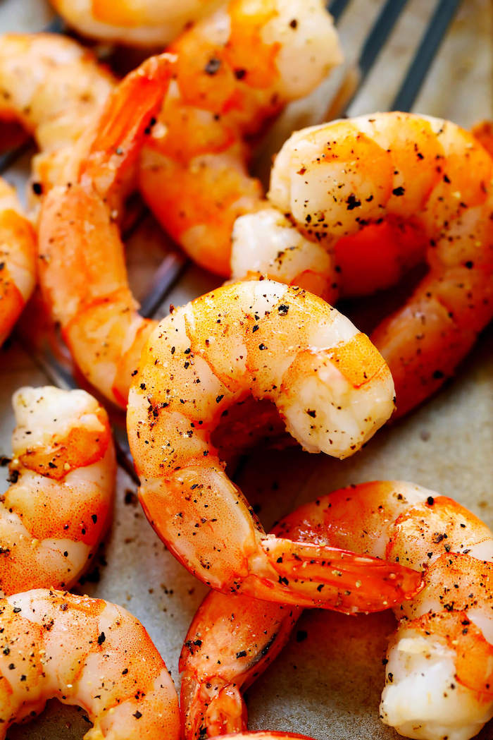 close up photo of baked shrimp garnished with herbs shrimp dinner ideas placed on paper lined baking sheet