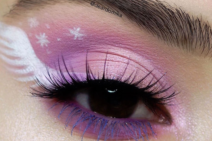 close up photo of brown eye with thick eyebrows winged eyeliner tutorial with purple eyeshadow white wing drawn on the side of the eye