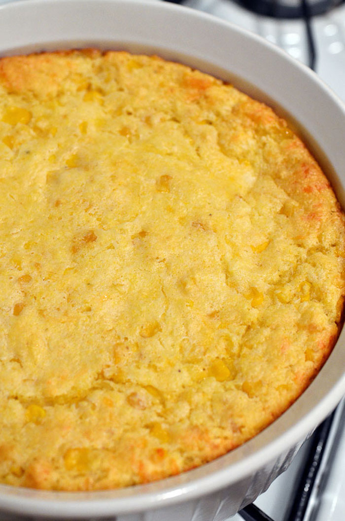 close up photo of corn casserole baked in white round casserole dish easy thanksgiving side dishes