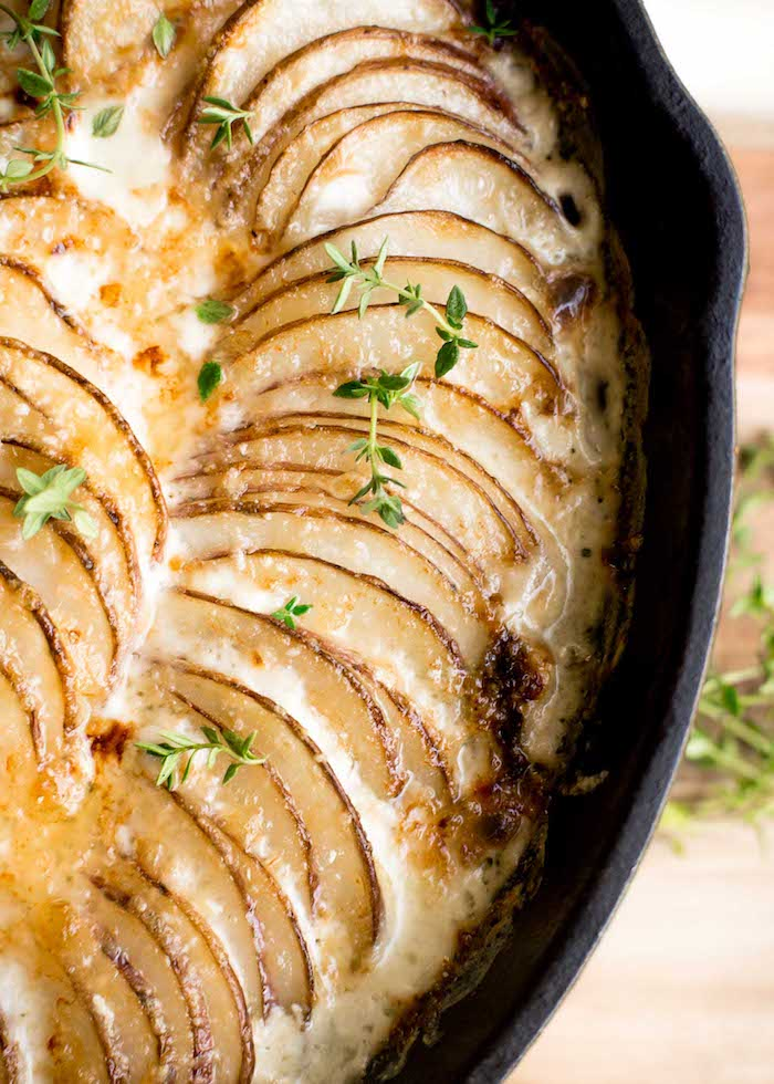 close up photo of creamy potatoes au gratin best thanksgiving side dishes baked in black skillet