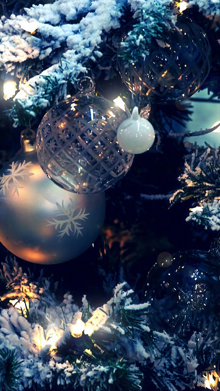 close up photo of decorated christmas tree covered with snow aesthetic christmas wallpaper silver baubles string of fairy lights