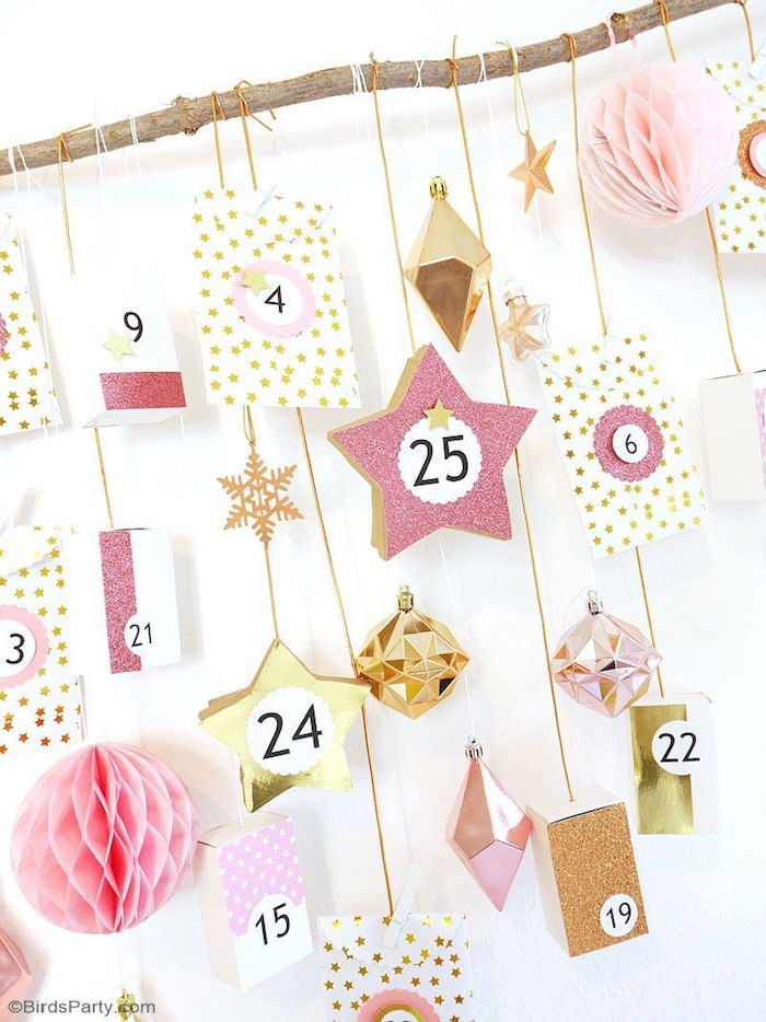 close up photo of homemade advent calendar boxes hanging with white and gold strings from small wooden branch