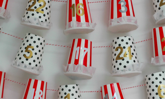 close up photo of paper cups white with black dots and red and white stripes homemade advent calendar labeled with numbers