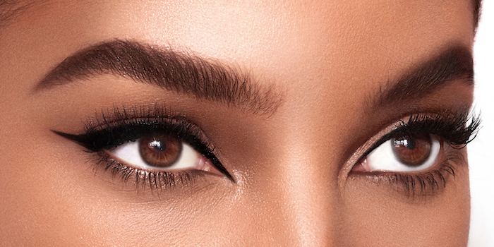 close up photo of woman with brown eyes light brown eyebrows cat eye makeup with black eyeliner