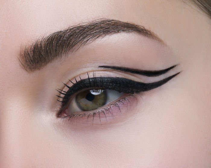 close up photo of woman with green eyes dark brown eyebrows cat eye eyeliner negative space eyeliner with two lines