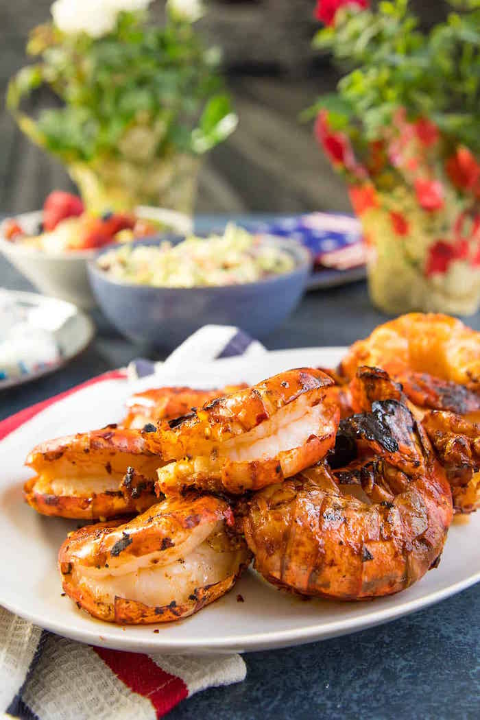 colossal grilled shrimp with harissa marinade placed on white plate shrimp recipes placed on dark granite table