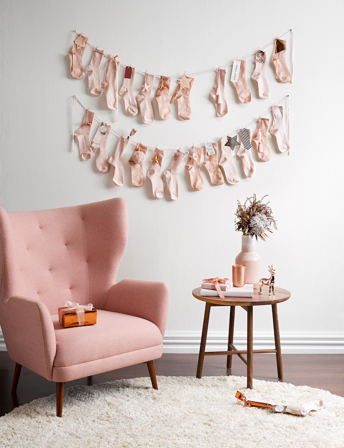 couch in pink next to wood side table advent calendar ideas white wall with two strings hanging on it with pink socks with treats inside