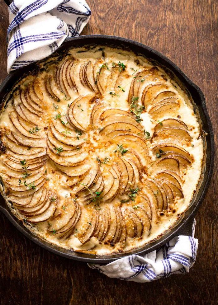 creamy potatoes au gratin best thanksgiving side dishes baked in black skillet placed on wooden surface