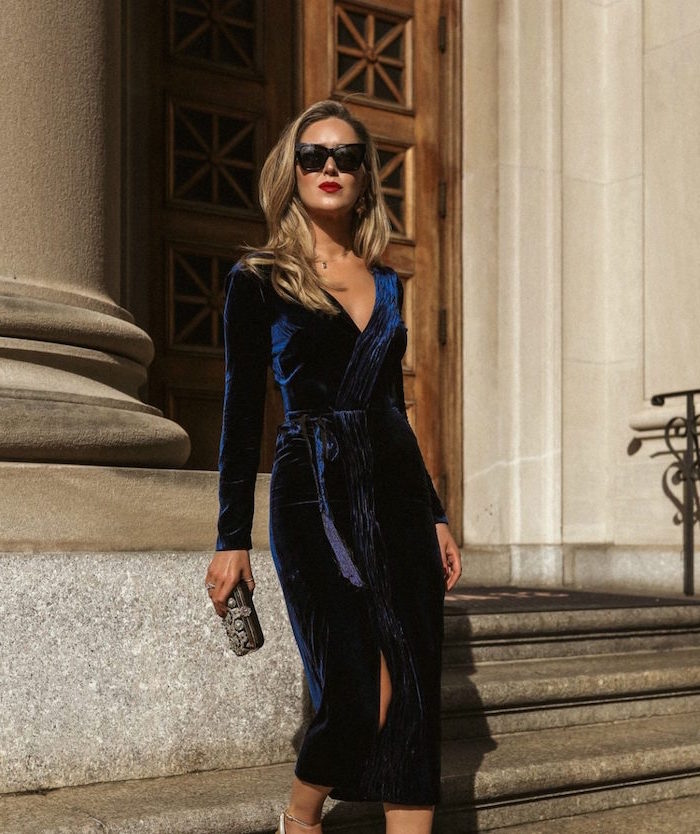 dark blue velvet wrap around dress with v neckline worn by woman with blonde hair how to dress for a wedding wearing sunglasses