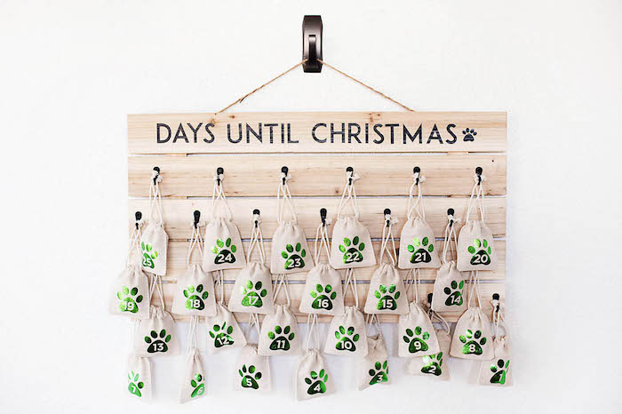 days until christmas written on wooden board hanging on white wall advent calendar small bags hanging decorated with numbers from one to twenty five