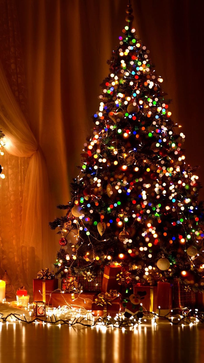 decorated christmas tree with lots of colorful lights merry christmas wallpaper presents underneath the tree