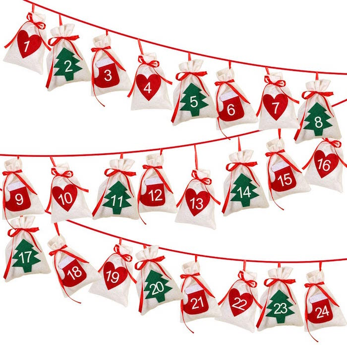 diy advent calendar red string hanging on white wall lots of bags attached to it with numbers from one to twenty four