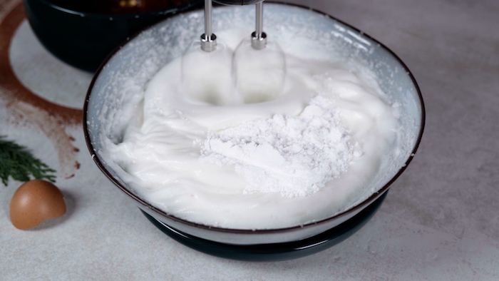 egg whites and powdered sugar being bitten together with a hand mixer christmas dinner party ideas in gray ceramic bowl