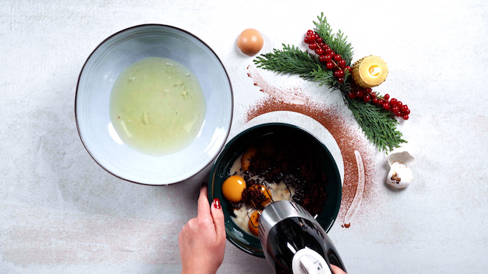 egg yolks being beaten with brown sugar in ceramic bowl christmas dinner party ideas egg whites in another bowl