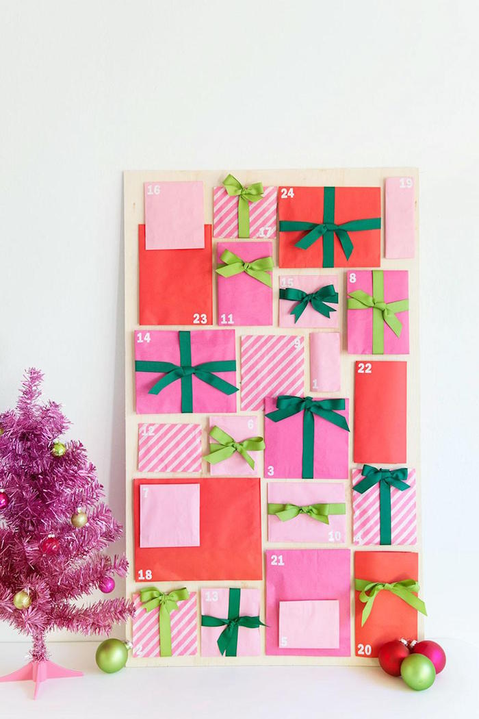 faux pink christmas tree next to unique advent calendars with paper bags filled with candy leaning on white wall