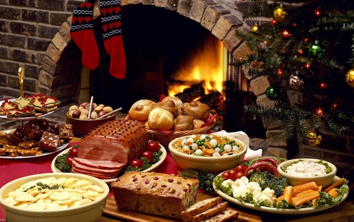 fireplace next to christmas tree christmas eve dinner ideas table with red table cloth lots of different dishes on the table