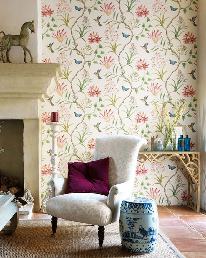 fireplace with white armchair in front of it placed on white carpet vintage wallpaper with floral motifs on the wall next to the fireplace