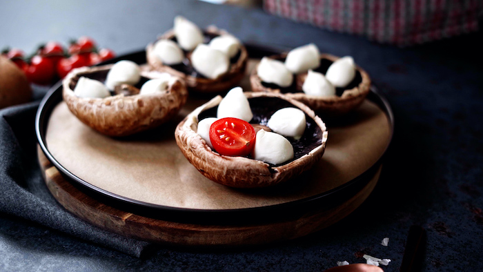 four portobello mushrooms stuffed with baby mozzarella cherry tomatoes thanksgiving side dish recipes placed on paper lined baking sheet