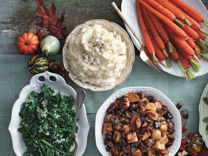 four thanksgiving side dishes on white plates on blue wooden surface mashed potatoes stuffing carrots kale salad