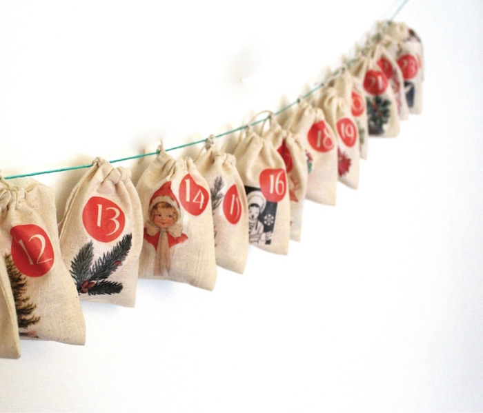 fun advent calendars blue string hanging on white wall with small bags with different decorations and numbers