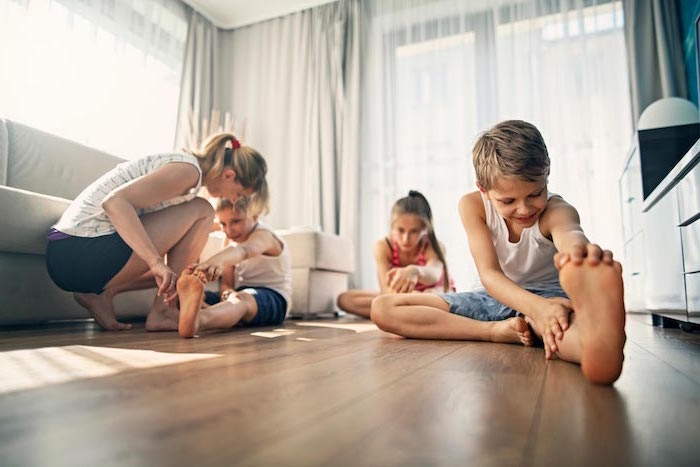 fun things to do at home two boys one girl and mom sitting on wooden floor stretching white curtains behind them