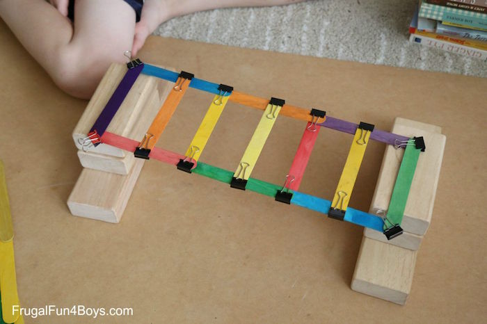 fun things to do with kids bridge built out of popsicle stickes painted in different colors on wooden blocks