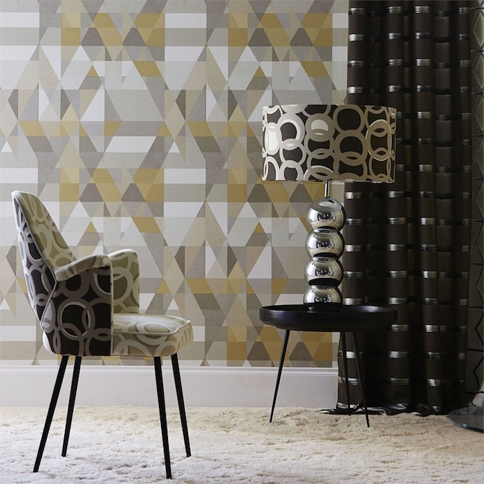 geometrical wallpaper in yellow gray white vintage wallpaper armchair with circles on it matching lampshade on black round metal table