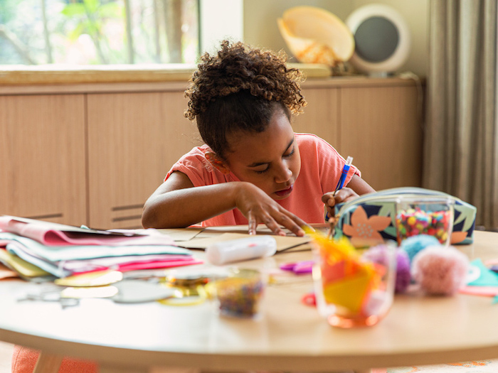 girl sitting at a table drawing activities for kids at home lots of craft supplies spread out on the wooden table
