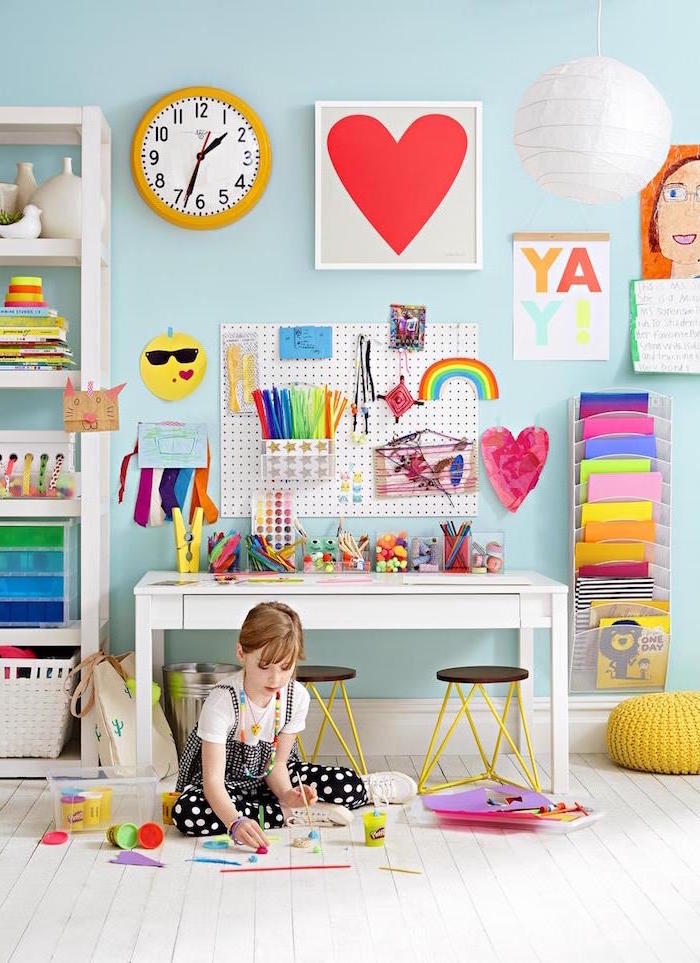 girl sitting on the floor in front of desk and cupboard filled with craft supplies fun things to do at home white wooden floor