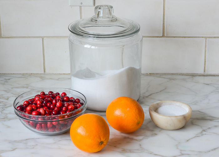 glass bowl with cranberries two lemons sugar christmas ham dinner cranberry sauce ingredients arranged on marble countertop