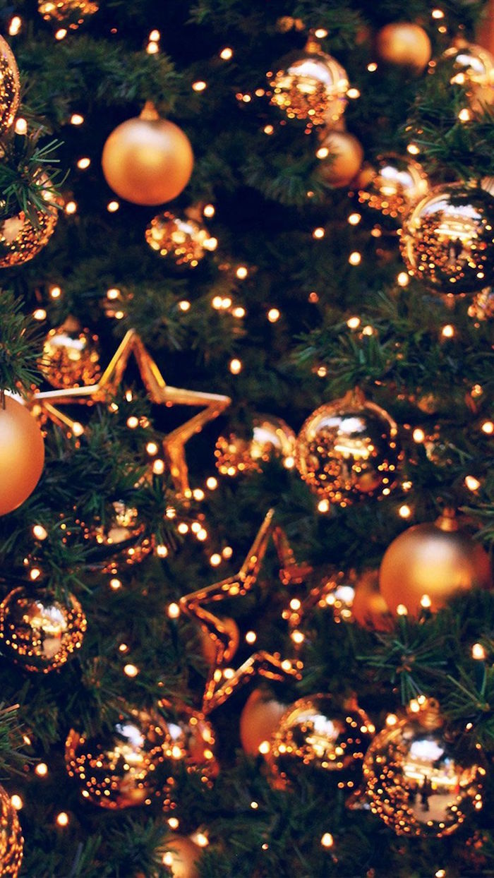 gold baubles and stars hanging on christmas tree decorated with fairy lights aesthetic christmas wallpaper close up photo